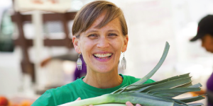 A brown haired woman with dangling earrings in a green shirt holding a leek