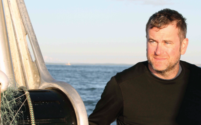 dark haired man in a black shirt with the ocean in the background