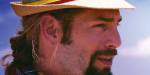 Man with goatee wearing a straw hat facing the side