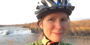 Photo of woman in a bike helmet by a river's small waterfall
