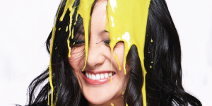 Dark, long haired woman with eyes closed and yellow liquid running down hair and face.